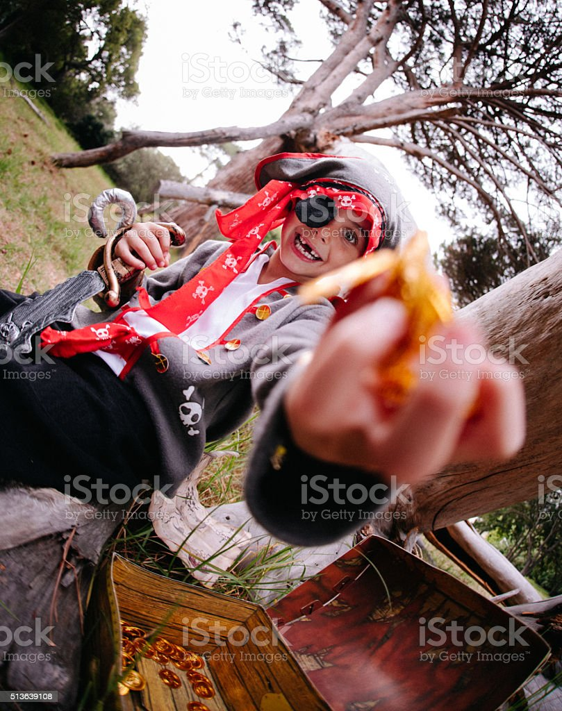 Boy dressing up pirate holding gold coins from treasure chest stock photo