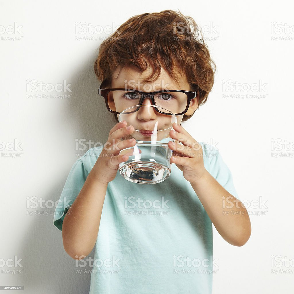 boy drinking a glass of water stock photo