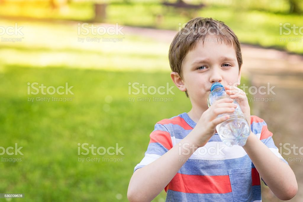 boy drinking mineral water from the plastic bottle stock photo