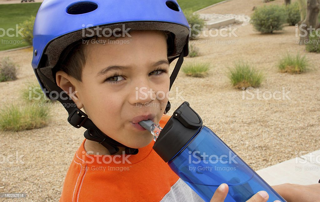 Boy drinking water and wearing helmet while outdoors stock photo