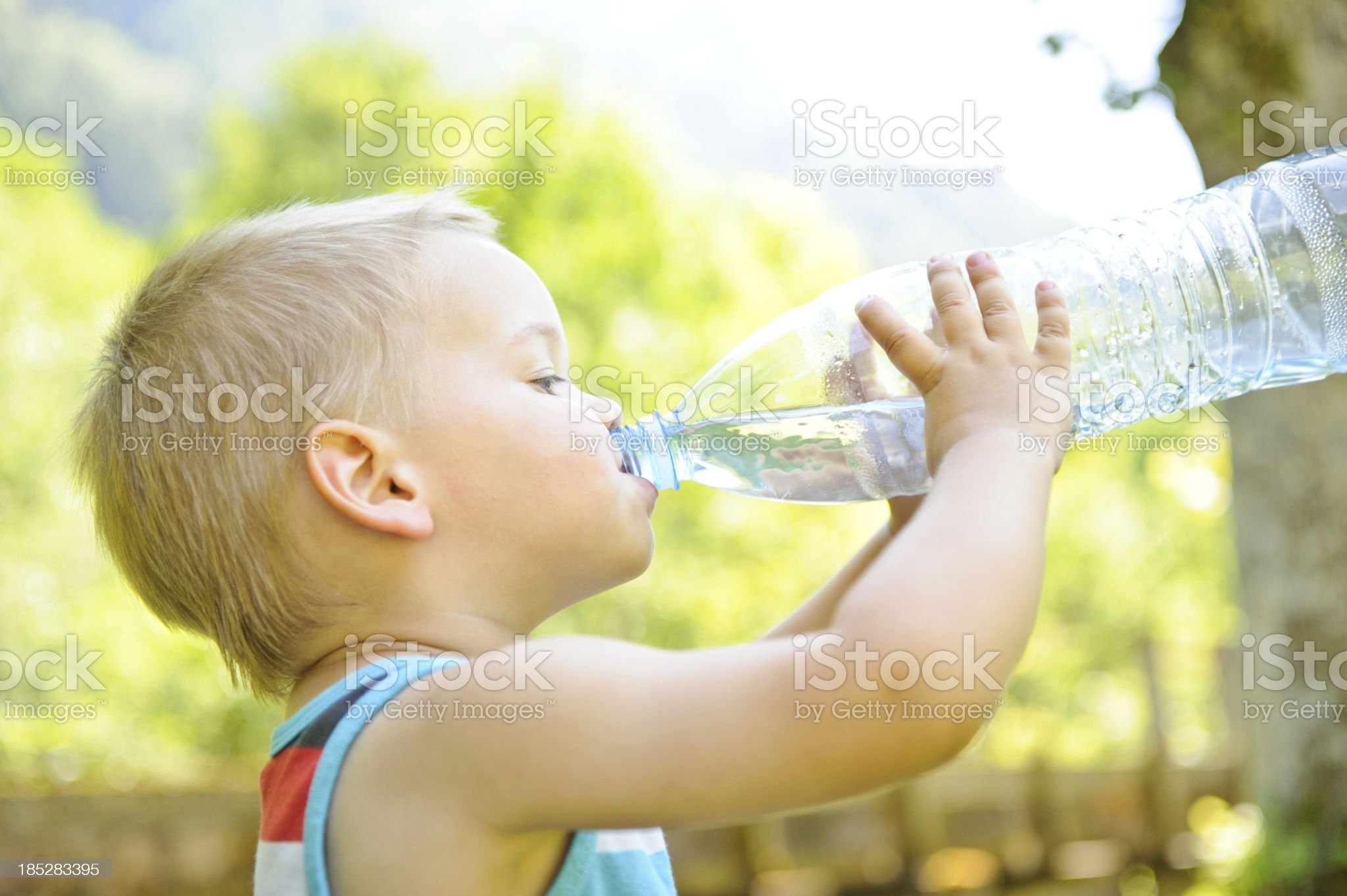 Boy drinking water from a clear bottle royalty-free stock photo