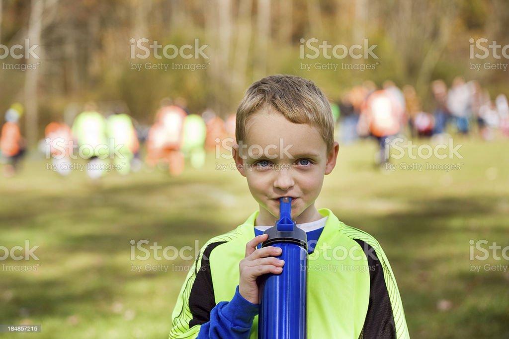 boy drinking water on soccer field stock photo