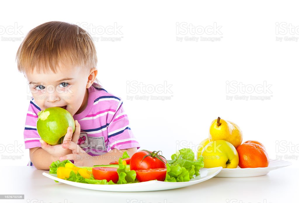 Boy eating apple next to a tray of fruits and vegetables royalty-free stock photo