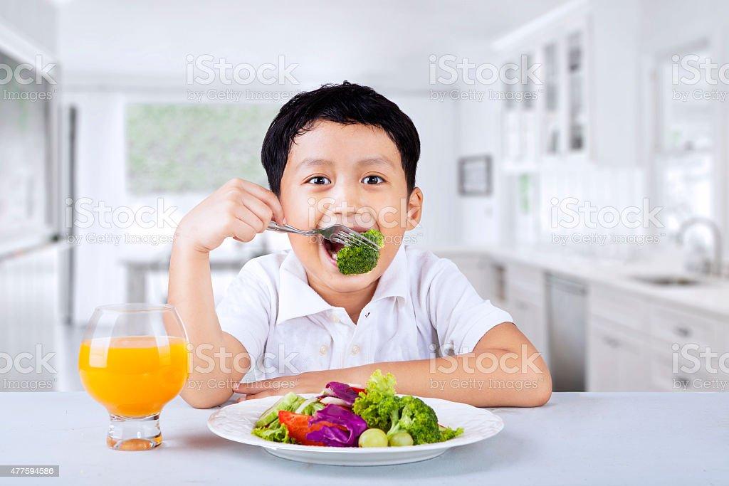 Boy eating broccoli at home stock photo
