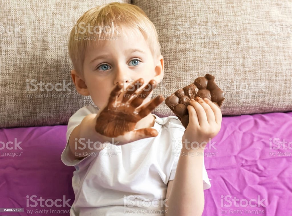 boy eating chocolate, holding a hand's candy, stock photo