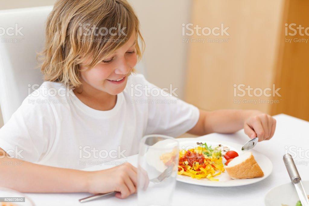 Boy eating dinner stock photo