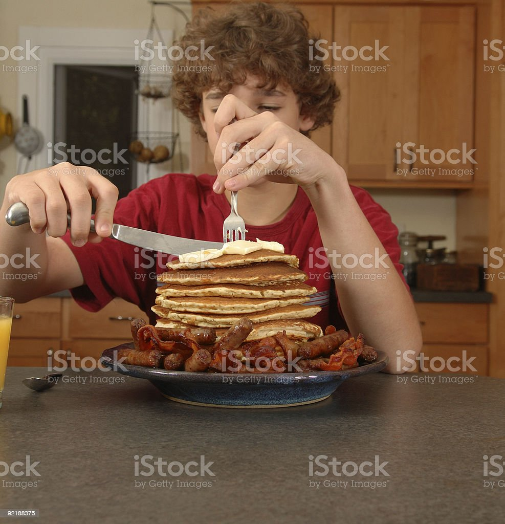 Boy eating huge breakfast royalty-free stock photo