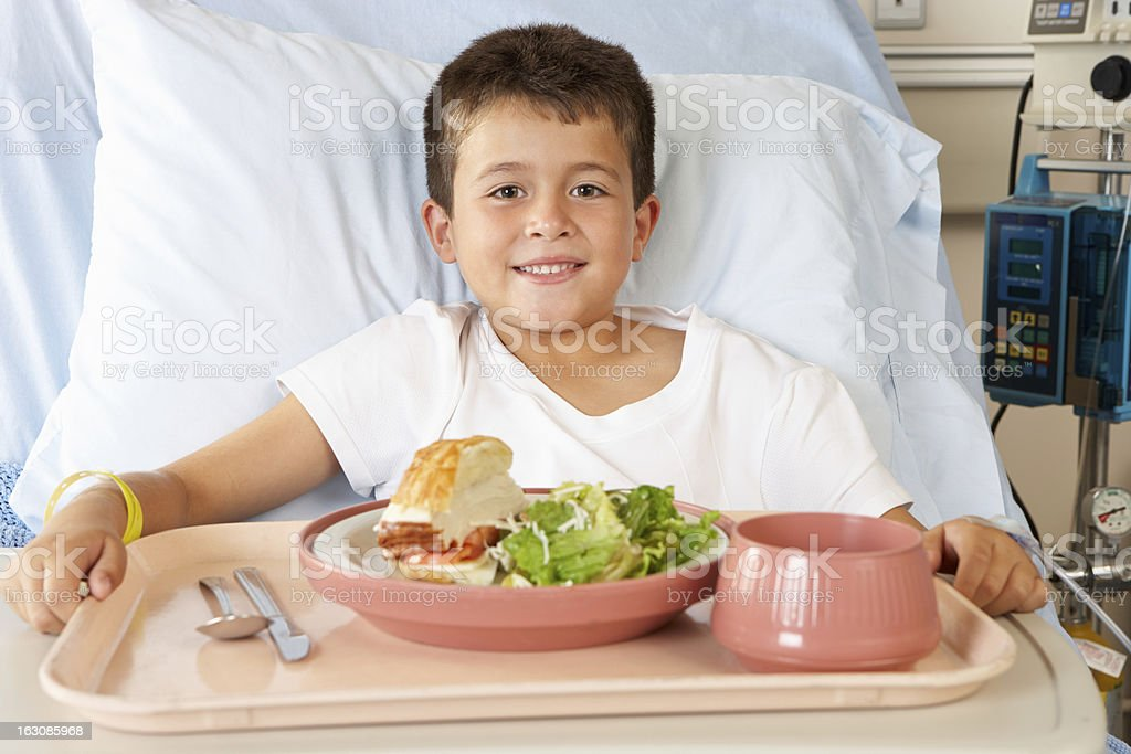 Boy Eating Meal In Hospital Bed stock photo