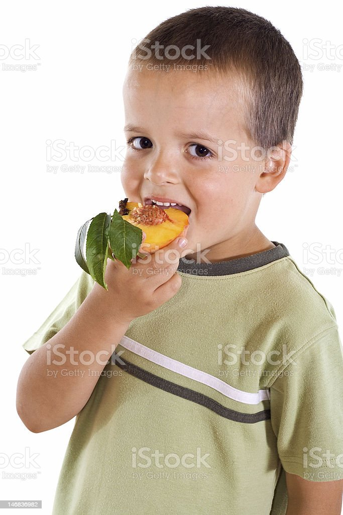 Boy eating peach royalty-free stock photo
