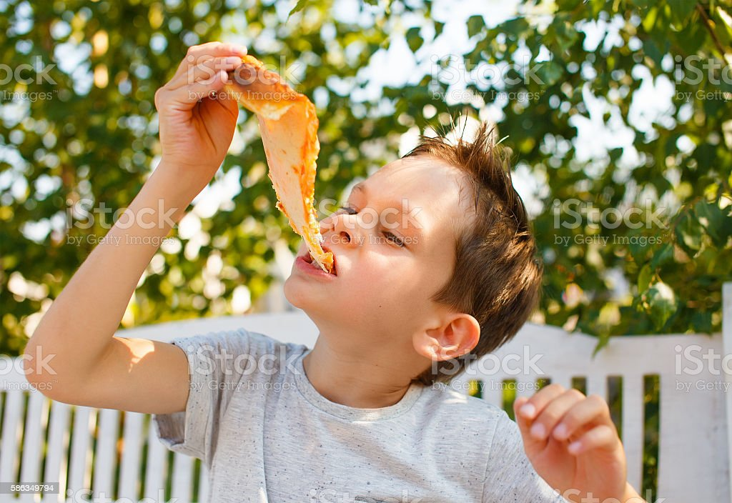 boy eating pizza stock photo