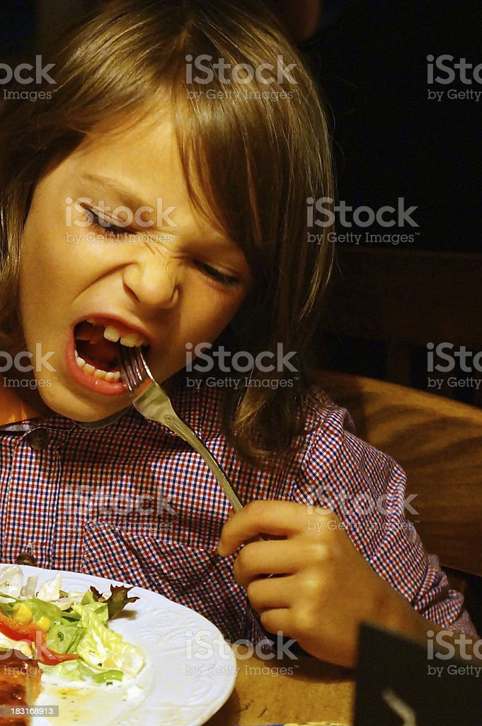 Boy eating salad stock photo