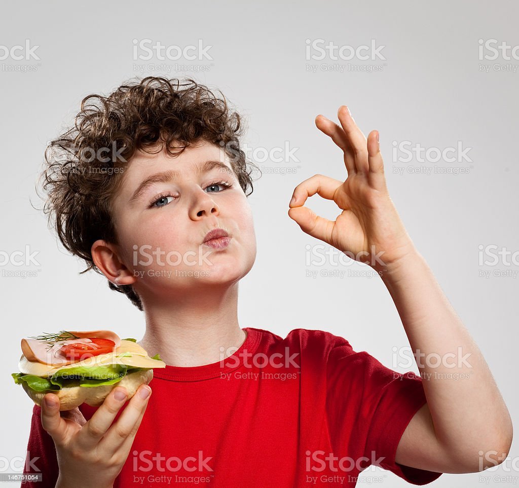 Boy eating sandwich showing OK sign royalty-free stock photo