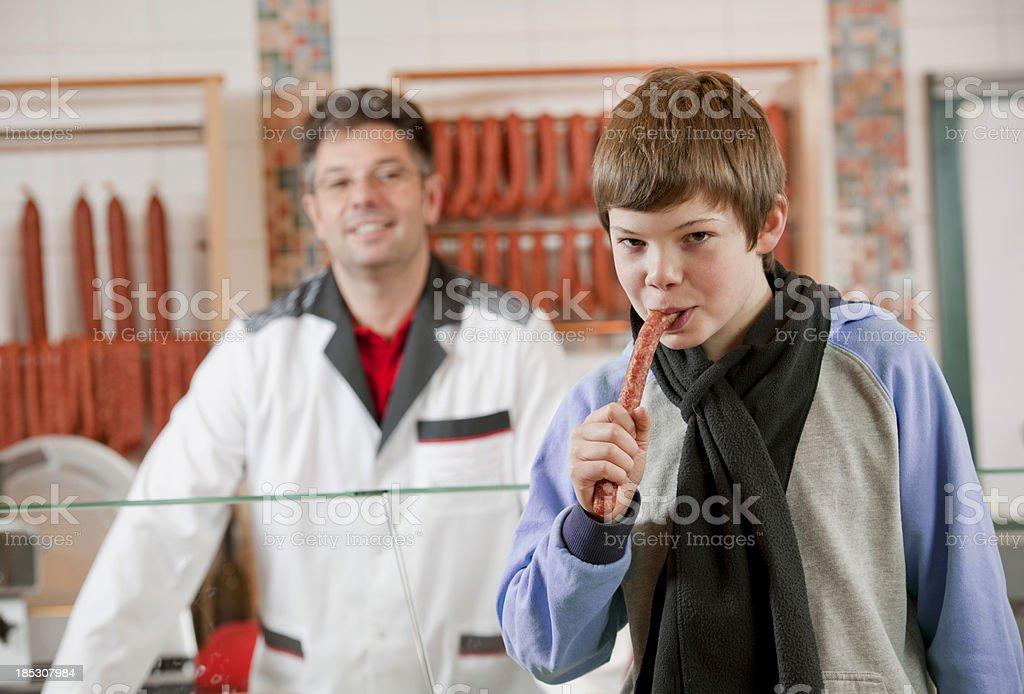 Boy eating sausage in supermarket royalty-free stock photo