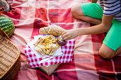 Boy eating strawberry jam on picnic