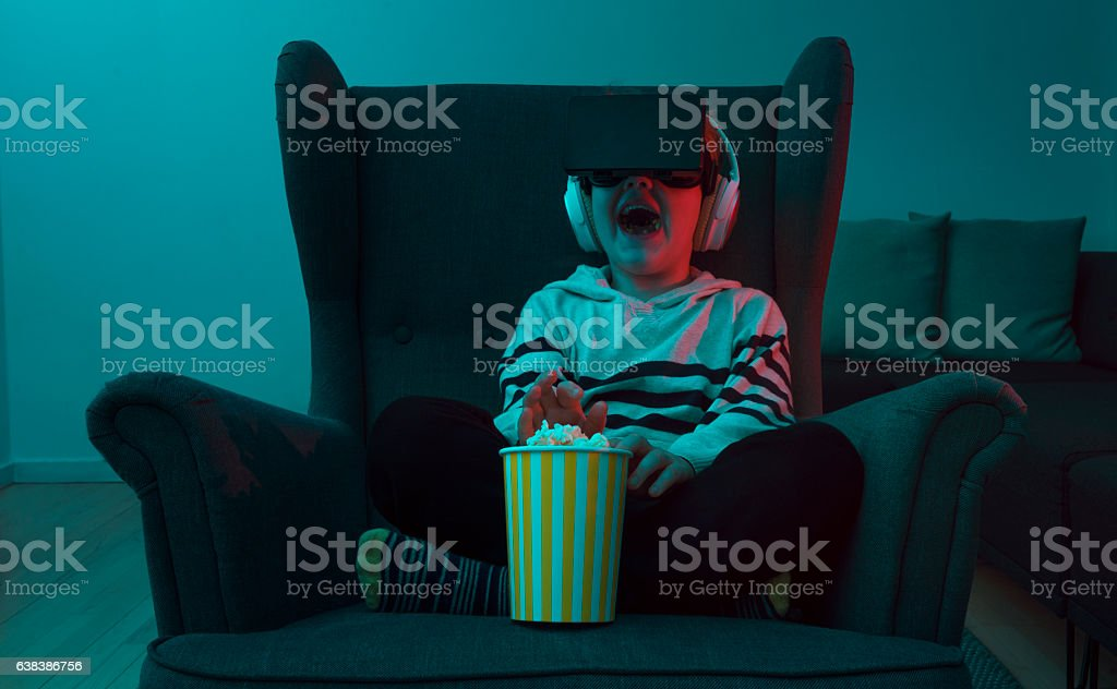 Boy eats popcorn while watching movie through VR glasses stock photo