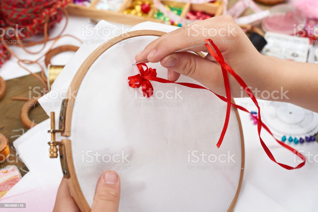 boy embroidered on the hoop, hand closeup and red ribbon on white textile, learns to sew, job training, handmade and handicraft concept stock photo