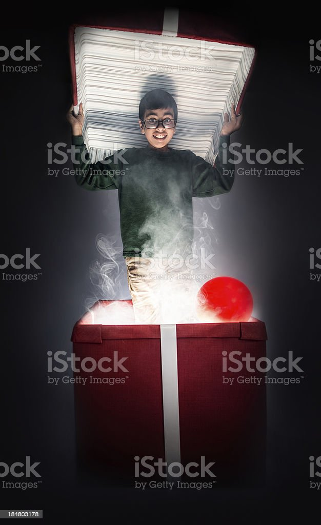 Boy emerging dramatically from giant present stock photo