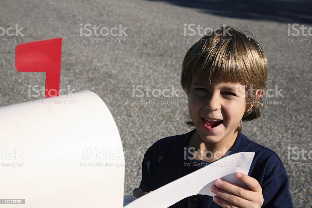 Boy excited with mail at mailbox stock photo