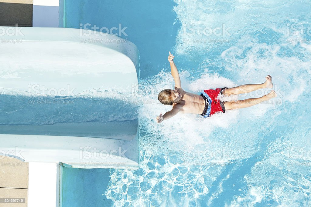 Boy Exiting Water Slide into Swimming Pool stock photo