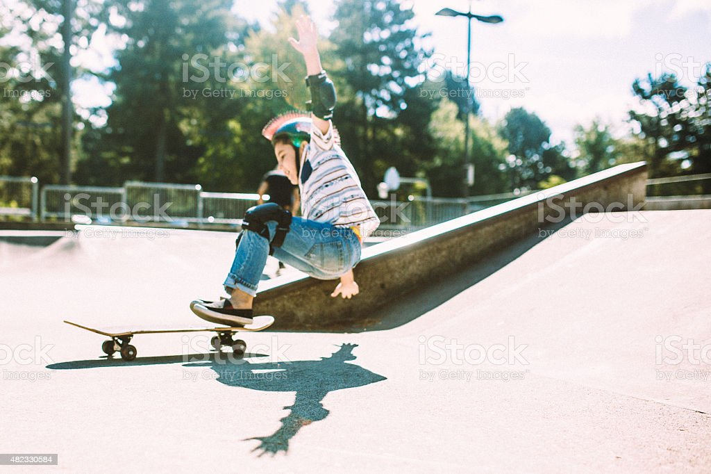 Boy Falling off Skateboard at Skate Park stock photo