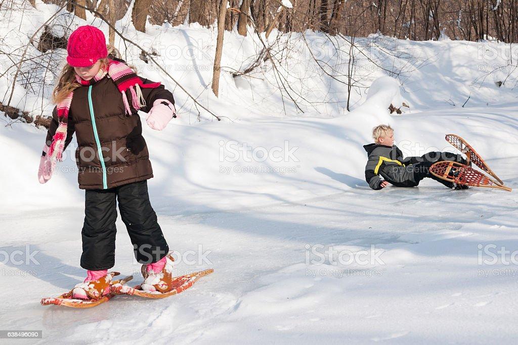Boy falls snowshoeing stock photo
