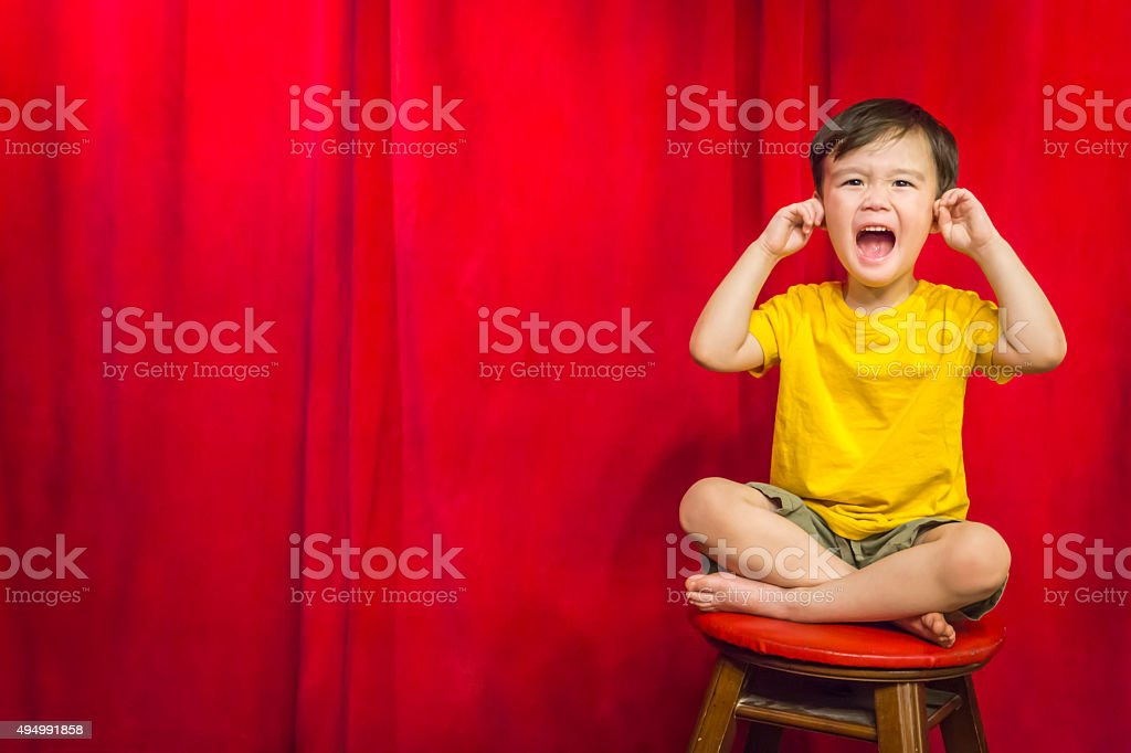 Boy, Fingers In Ears on Stool in Front of Curtain stock photo