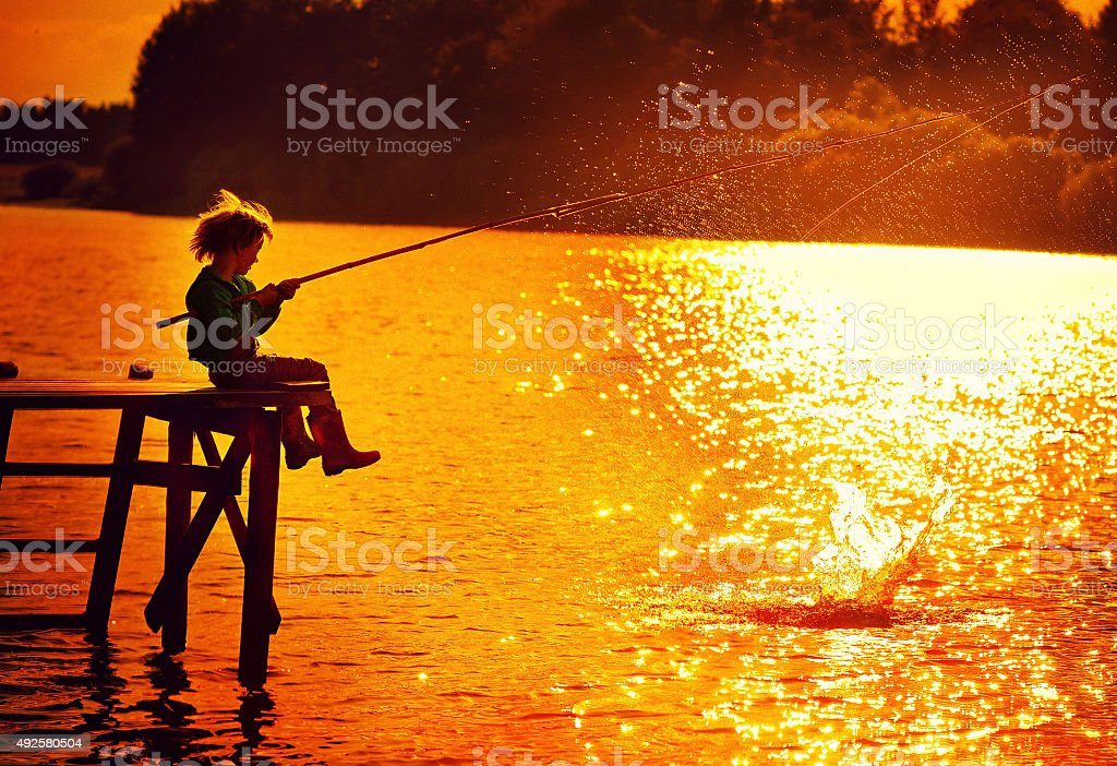 Boy fishing at sunset stock photo