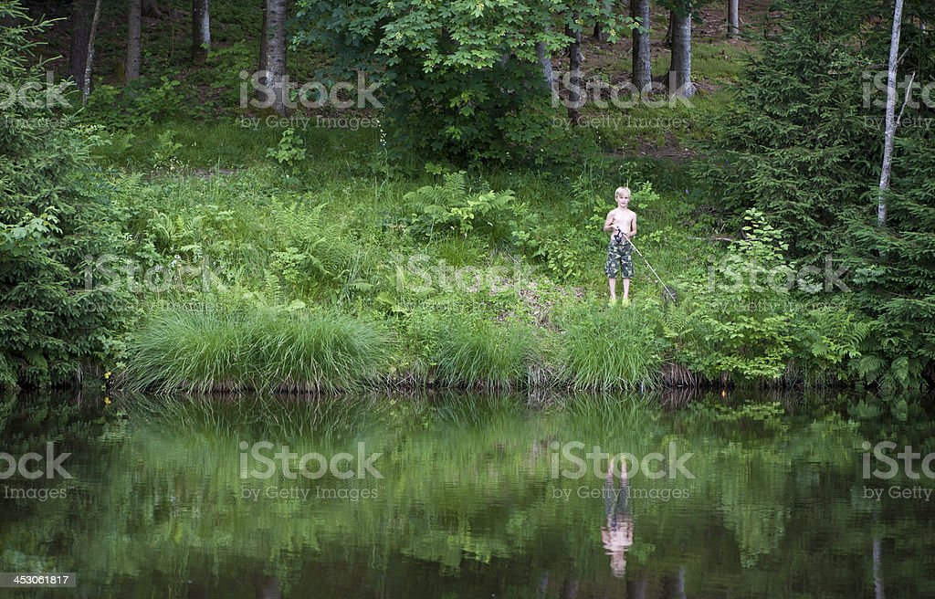 Boy fishing in a pond royalty-free stock photo
