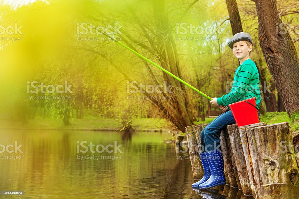 Boy fishing near beautiful pond with fishrod stock photo