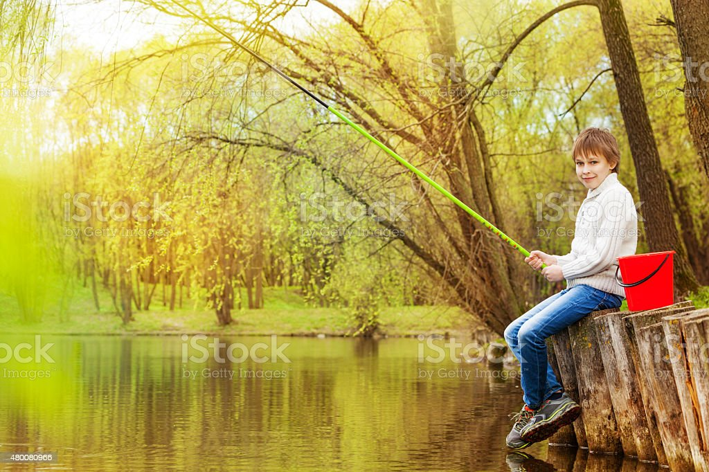 Boy fishing near the pond with green fishrod stock photo