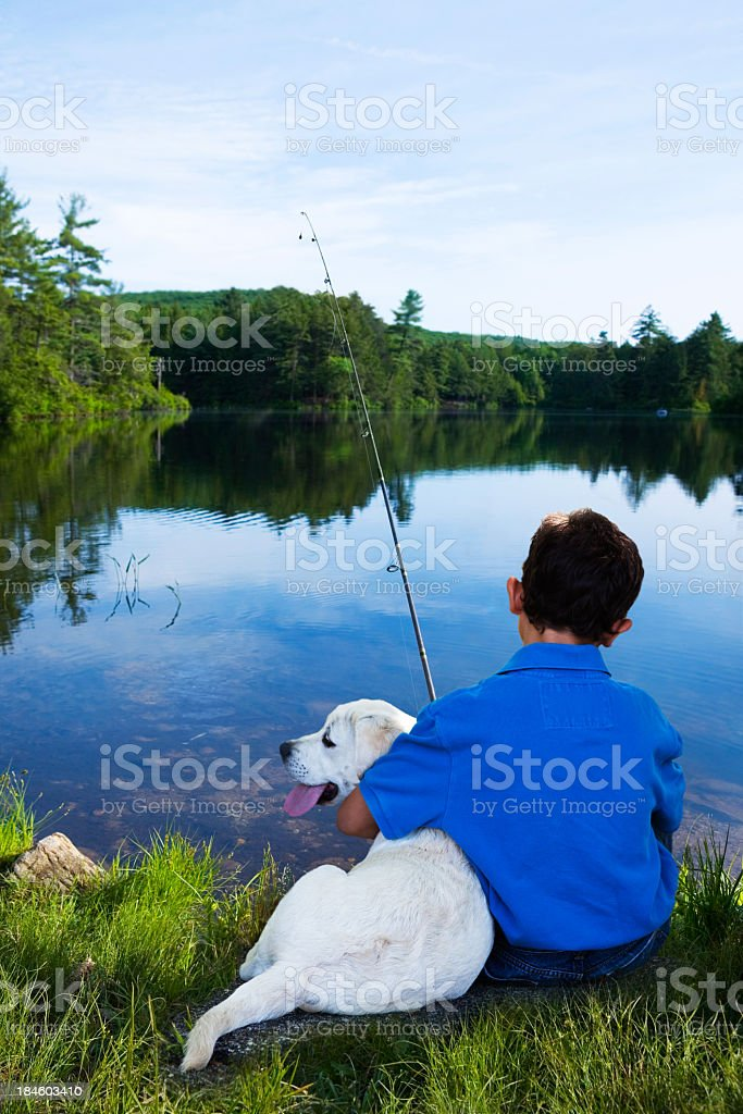 Boy fishing with his dog stock photo