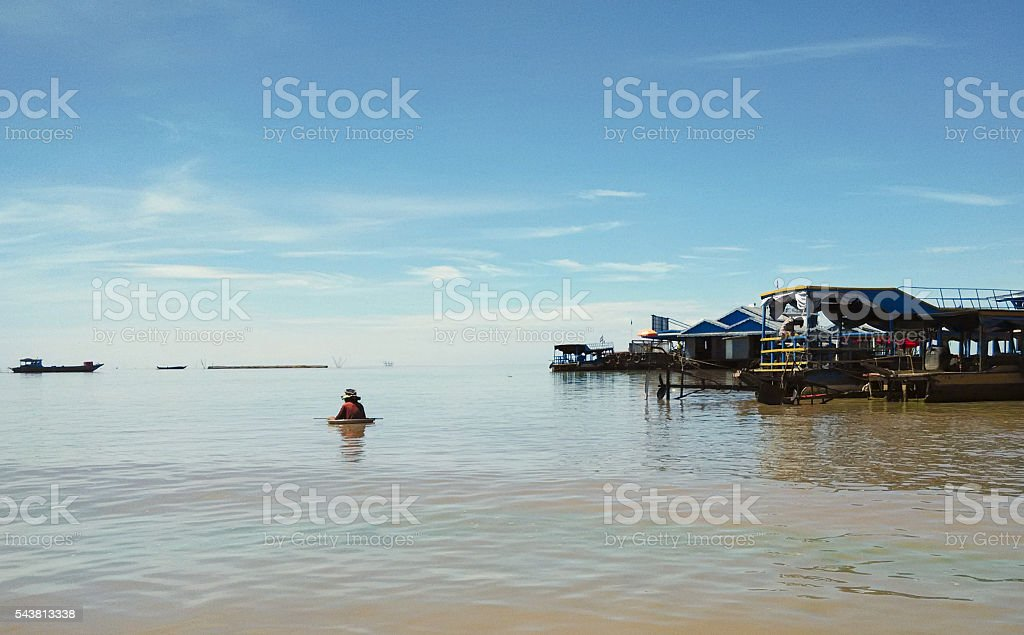Boy floating in a basin at Tonle Sap Lake stock photo