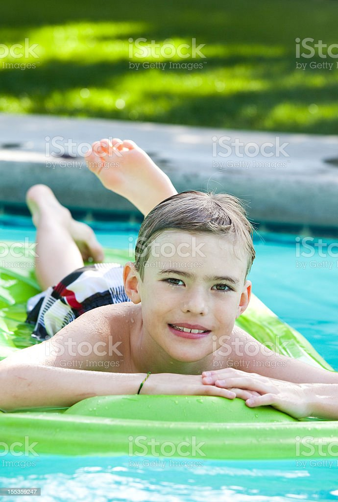 A happy young caucasian boy in a backyard swimming pool.