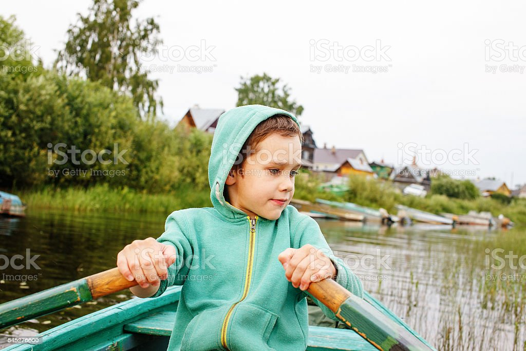 boy floats on a rowing boat to the shore stock photo