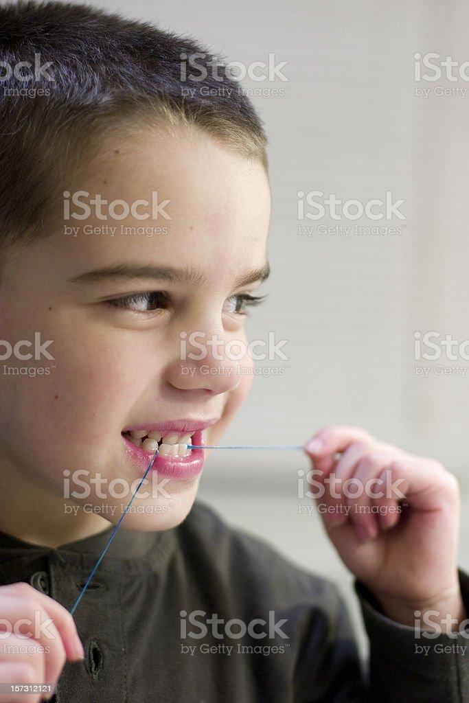 Boy flosses teeth stock photo