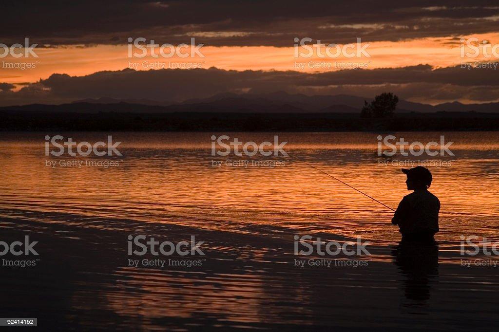 Boy Fly Fishing at Sunset stock photo