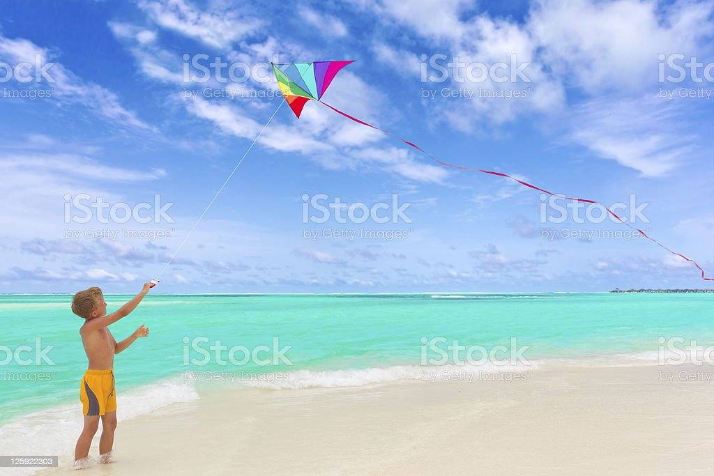 Boy flying kite on beach stock photo