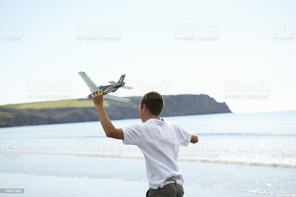Boy flying toy airplane on beach royalty-free stock photo