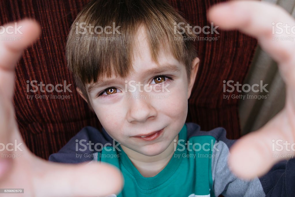 Boy framing a shot with his hands stock photo