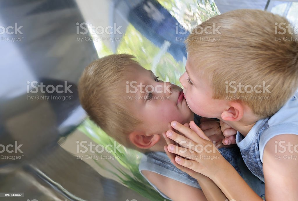Boy gazing on funny mirror stock photo
