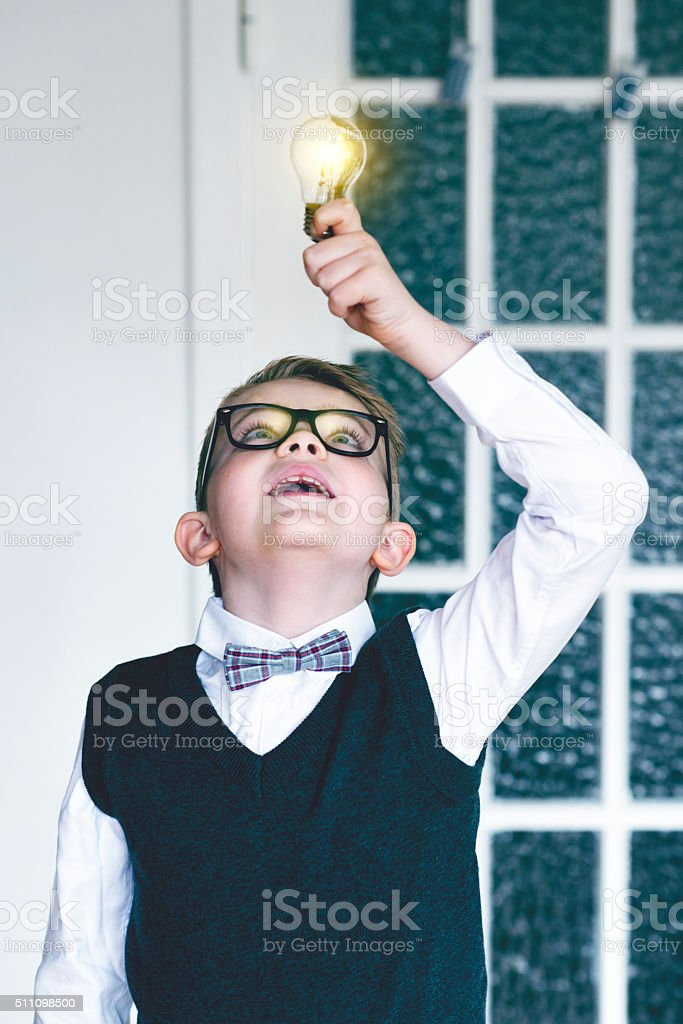 Boy gets idea and discover an invention with light bulb stock photo