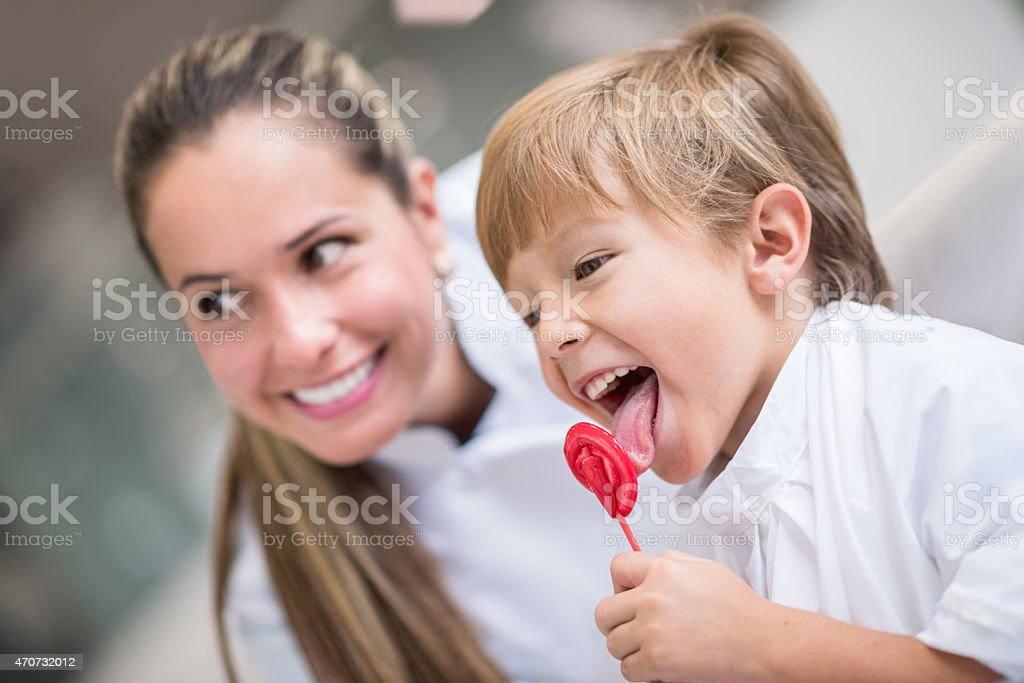 Boy getting a lollipop at the hairdresser or doctor stock photo