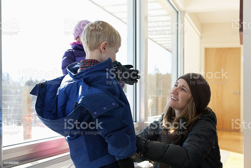 Boy getting dressed in winter clothing, mother helping stock photo