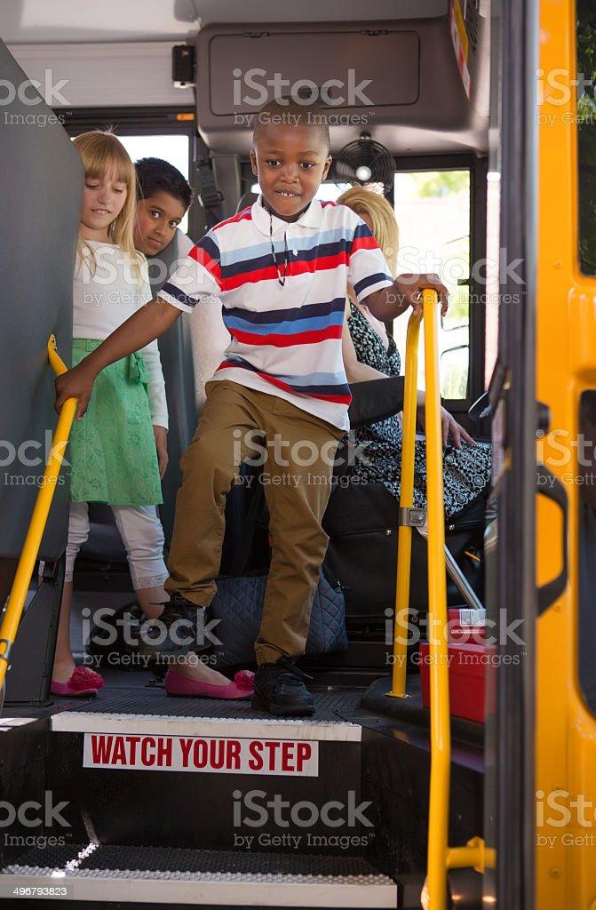 boy getting off school bus stock photo
