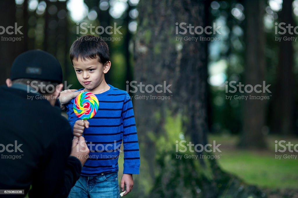 Boy getting offered a piece of candy by a stranger stock photo