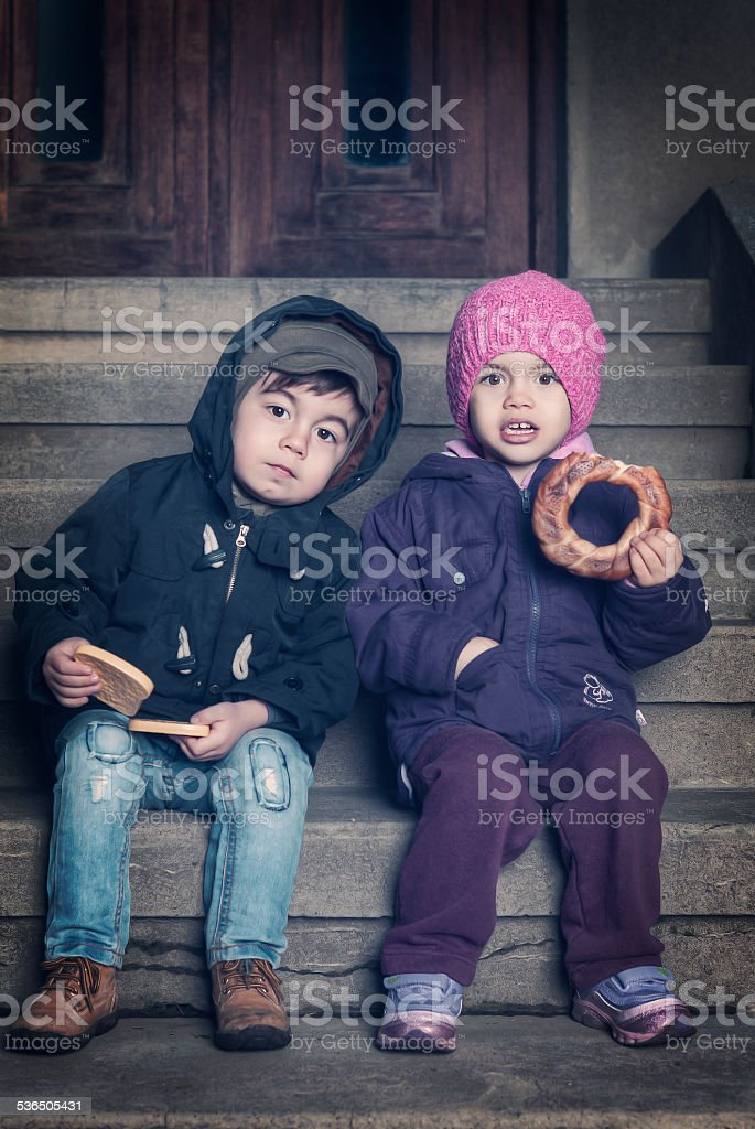 boy & girl eating outside bread stock photo