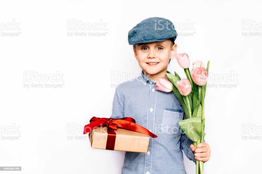 boy gives flowers and a gift stock photo