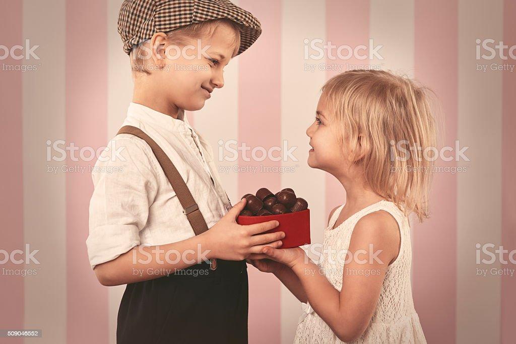 Boy giving a girl box full of chocolates stock photo