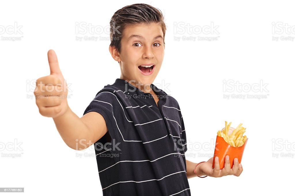 Boy giving a thumb up and holding bag of fries stock photo