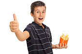 Boy giving a thumb up and holding bag of fries